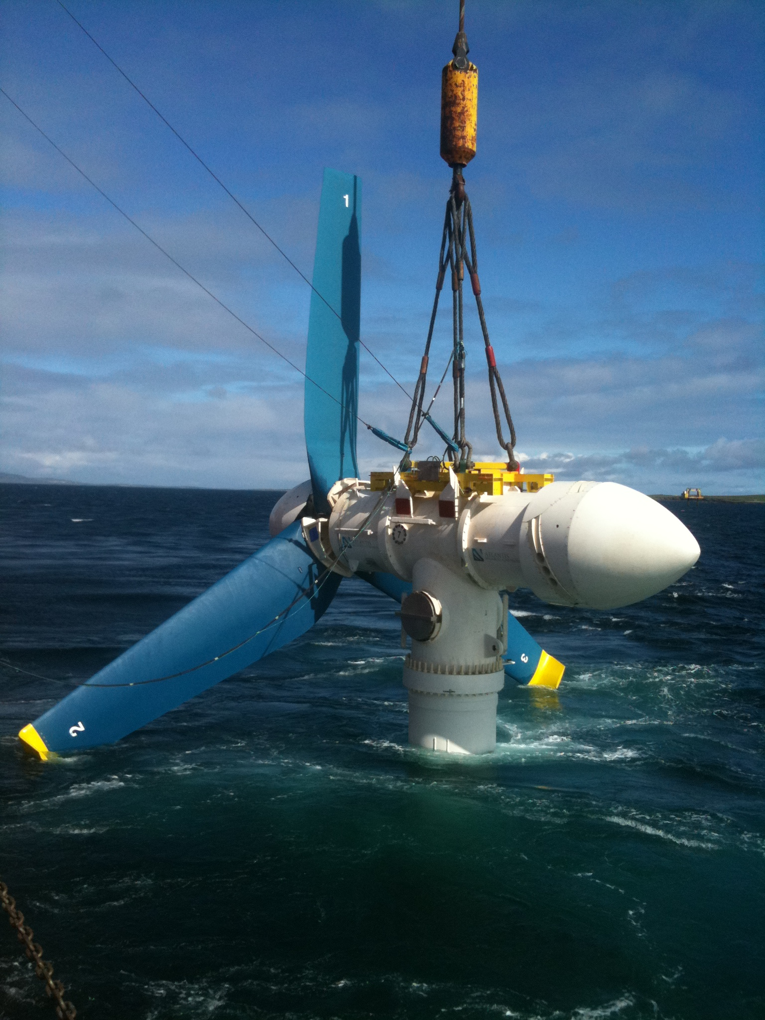 Figure 1 - An AR1000 tidal turbine is deployed at the European Marine Energy Centre in Orkney. The turbine section is carefully lowered into the water from the deck of the installing vessel using its crane.