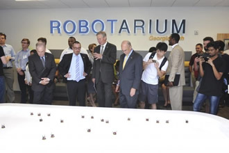 Robot cuts a ribbon to reveal the Robotarium